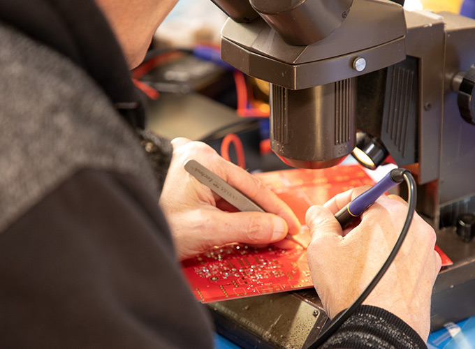 Image of Hutch soldering a circuit board for Radial's HDI direct box.